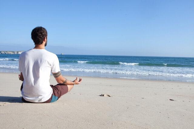 砂浜で座ってで瞑想をする男性