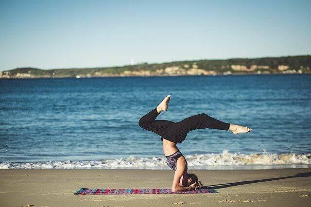 海辺で倒立してヨガをする女性