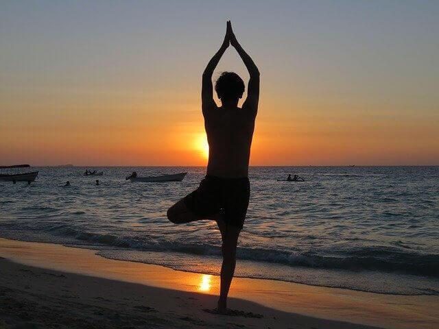 日没の海辺でヨガをする人