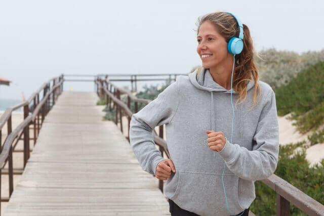 ヘッドフォンをしてジョギングする女性