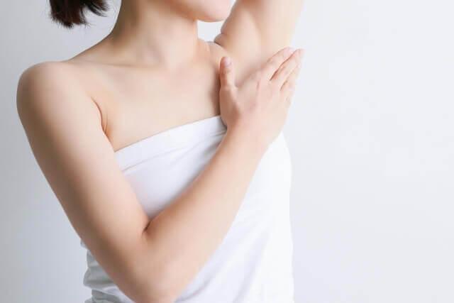 腋に手を当てる女性